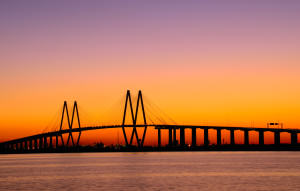Cable style bridge in Baytown, TX in front of an evening sunset sky.