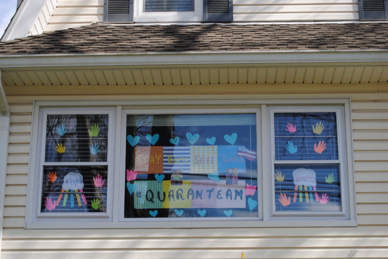 Home window decorated with positive Stay Home messages