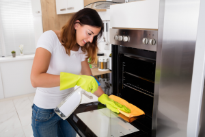 Woman cleaning glass door of oven