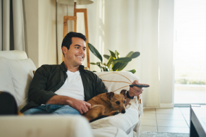 Smiling man relaxing on couch with his dog holding remote control in hand watching tv in living room.